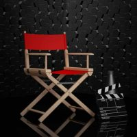 Cinema Industry Concept. Red Director Chair, Movie Clapper and Megaphone on a black background. 3d Rendering